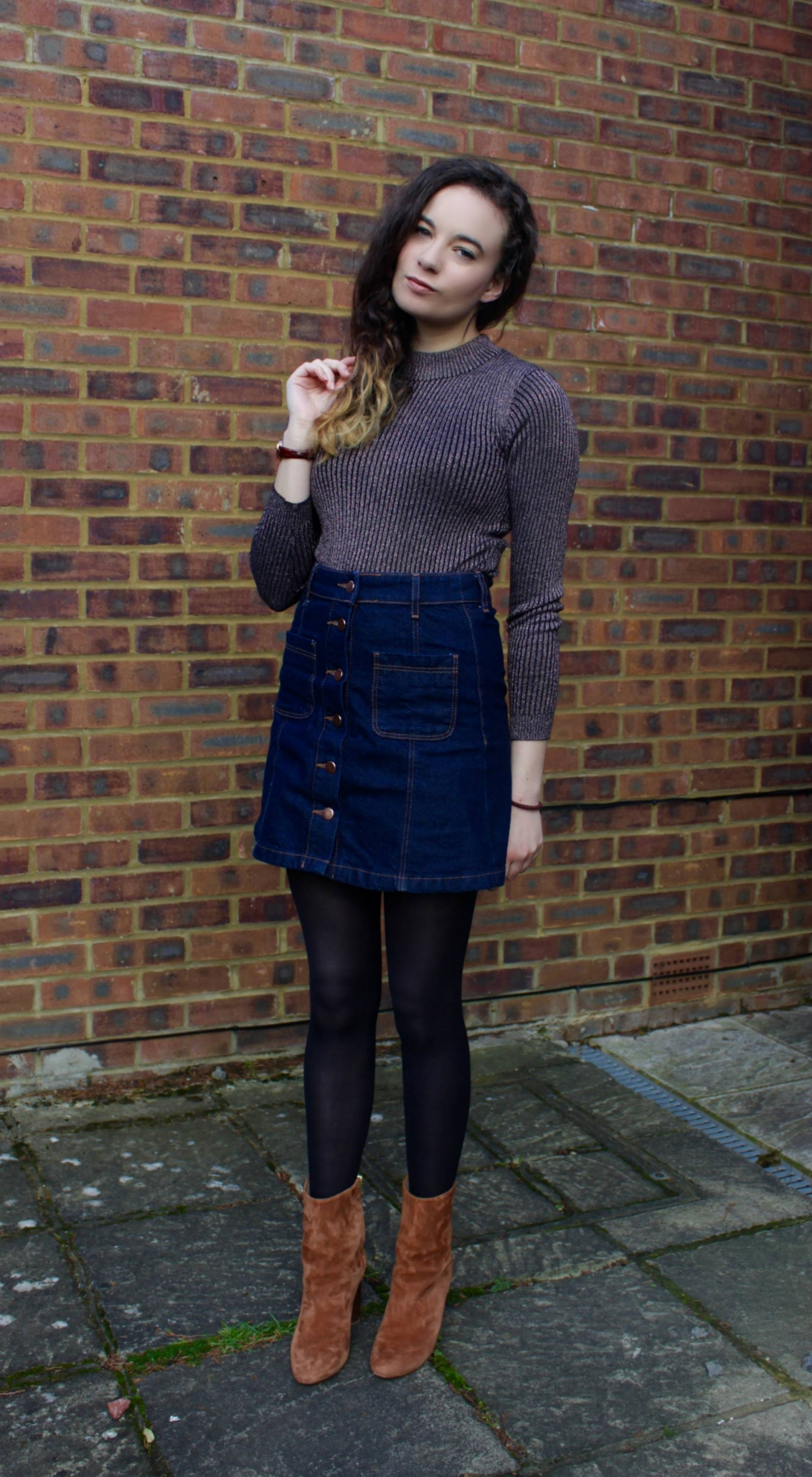 Denim skirt outfit with head tilted to the side
