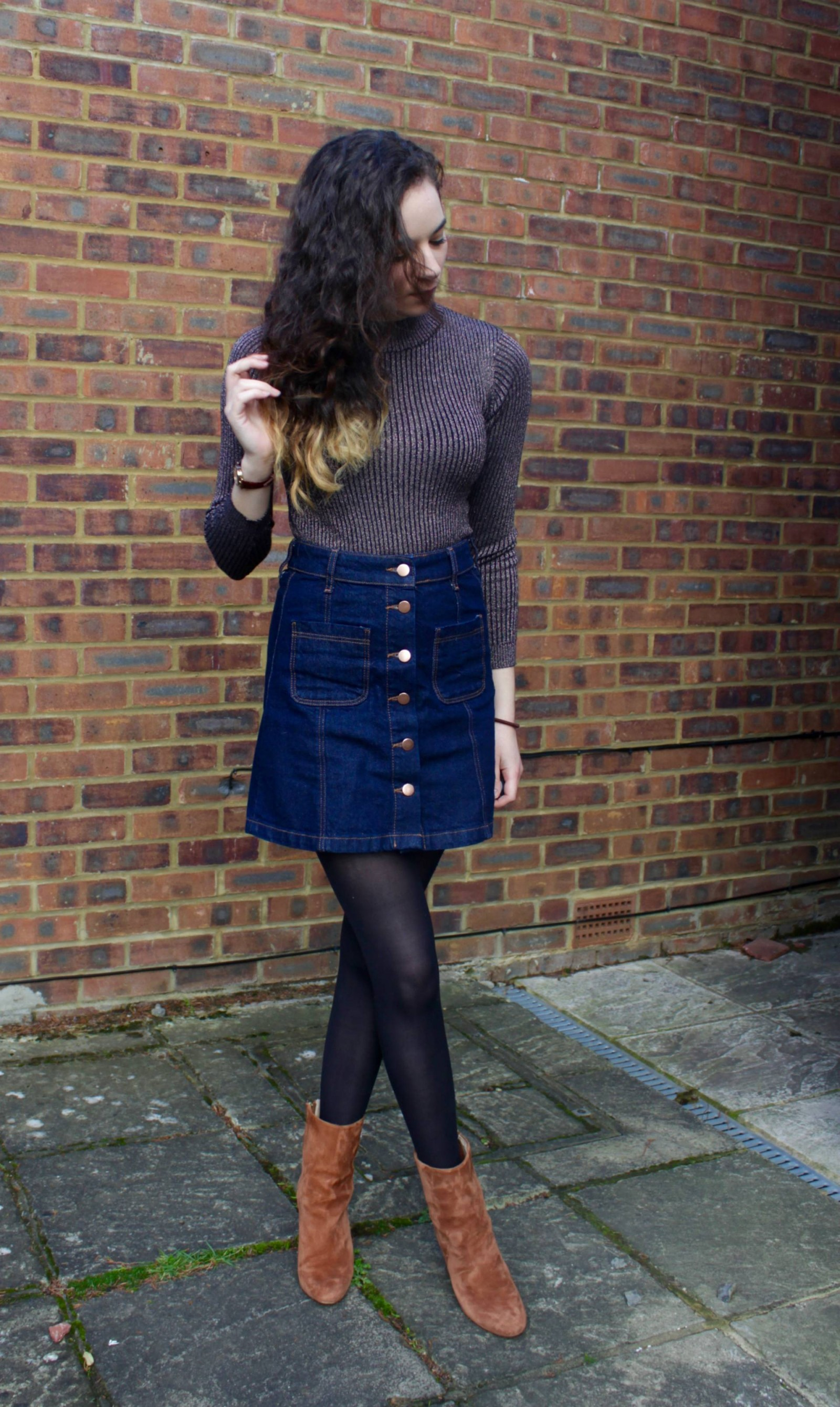 Denim skirt outfit with woman looking down