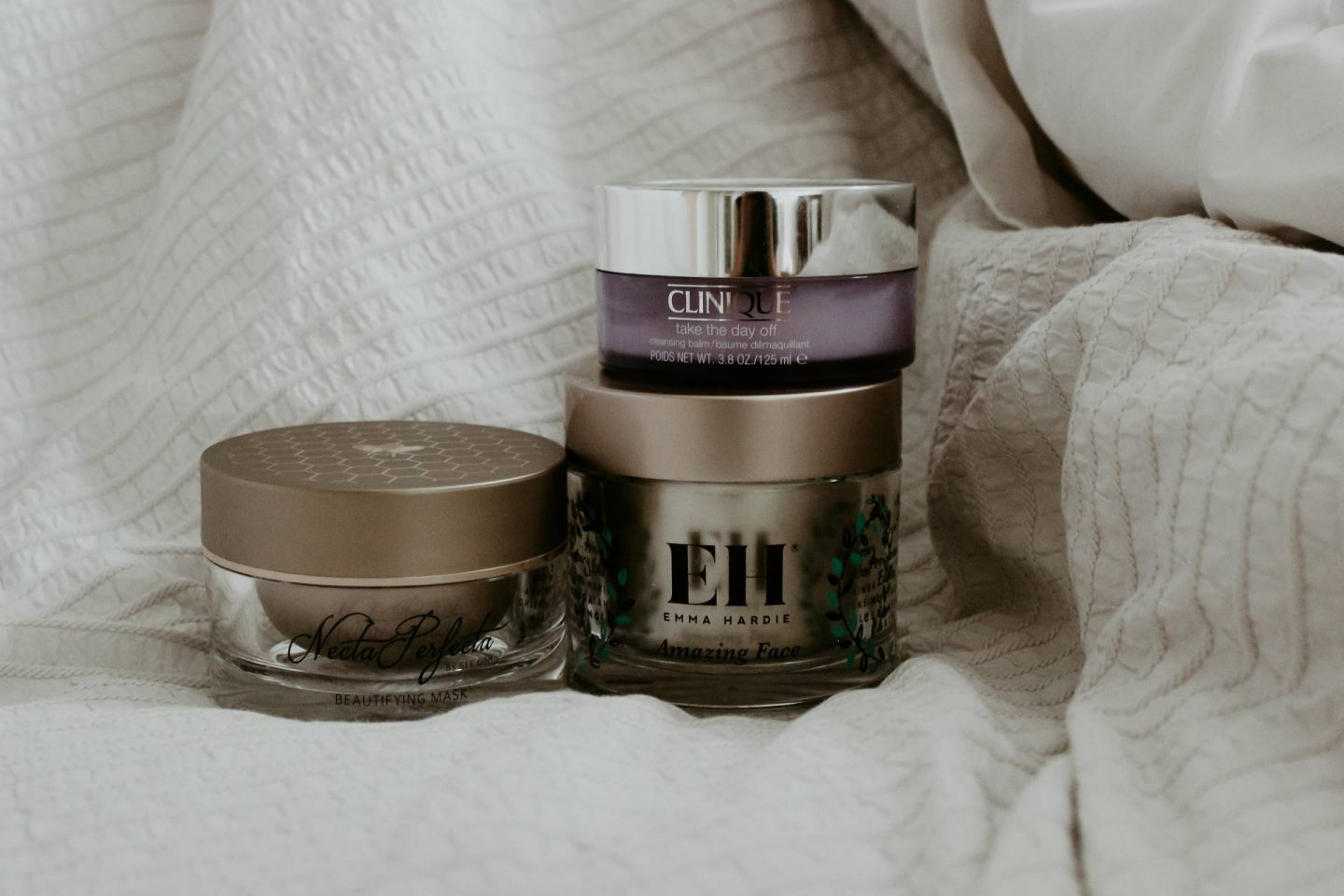 Cleansing balm stacked on white bedding