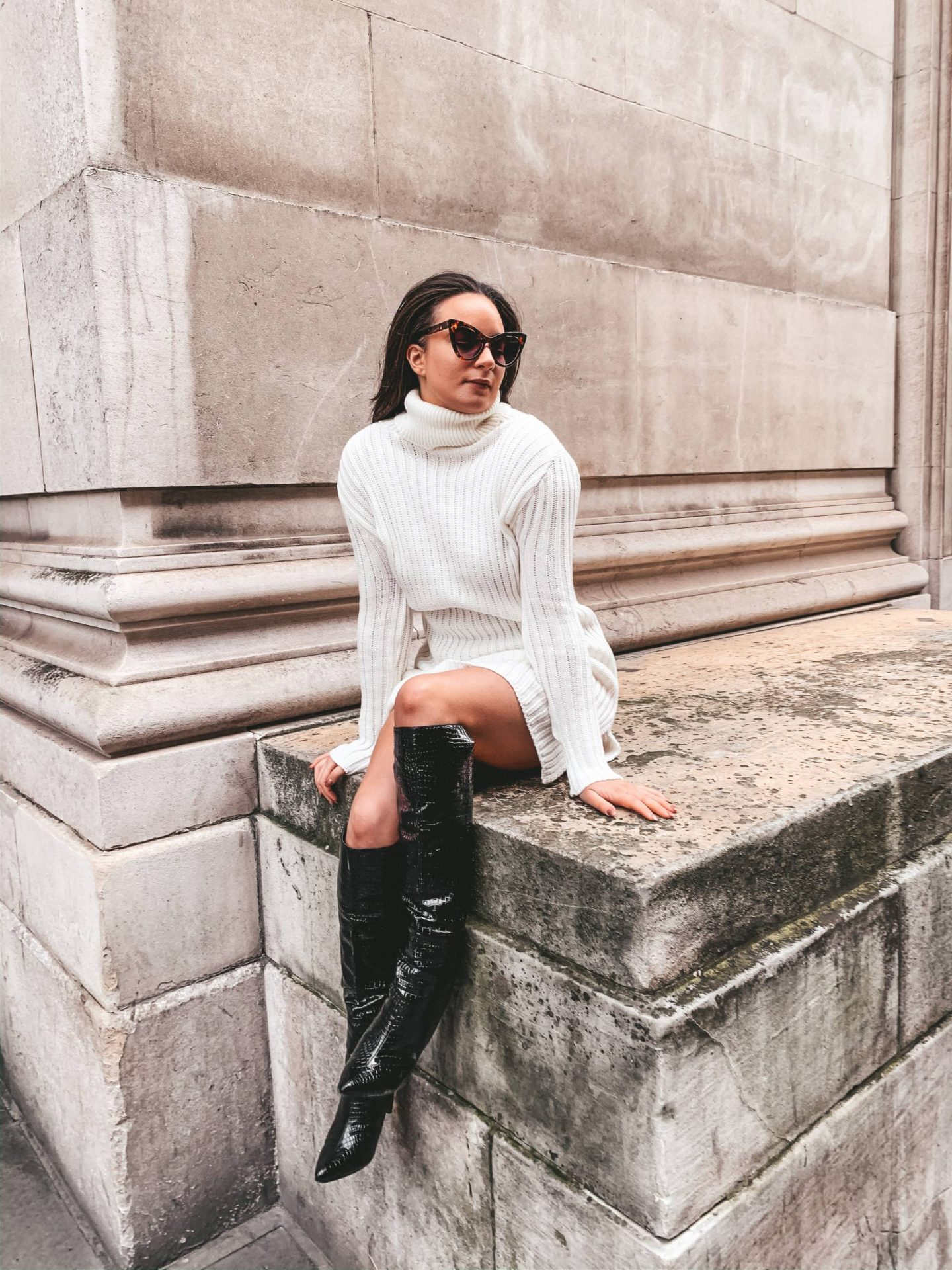 Jumper dress with black boots and sunglasses