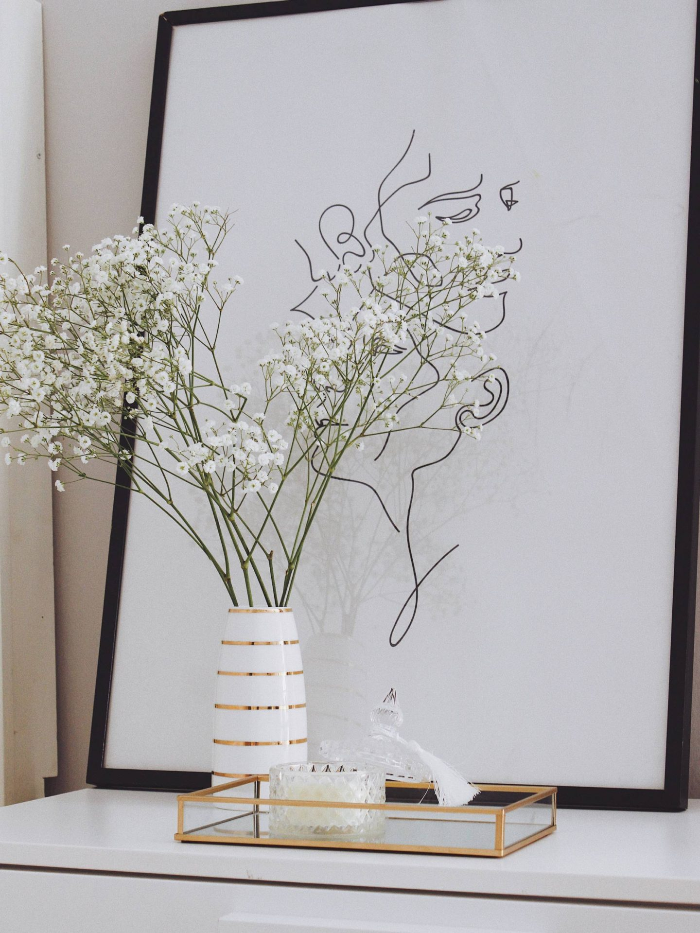 baby's breath flowers next to candle and print in rented living space