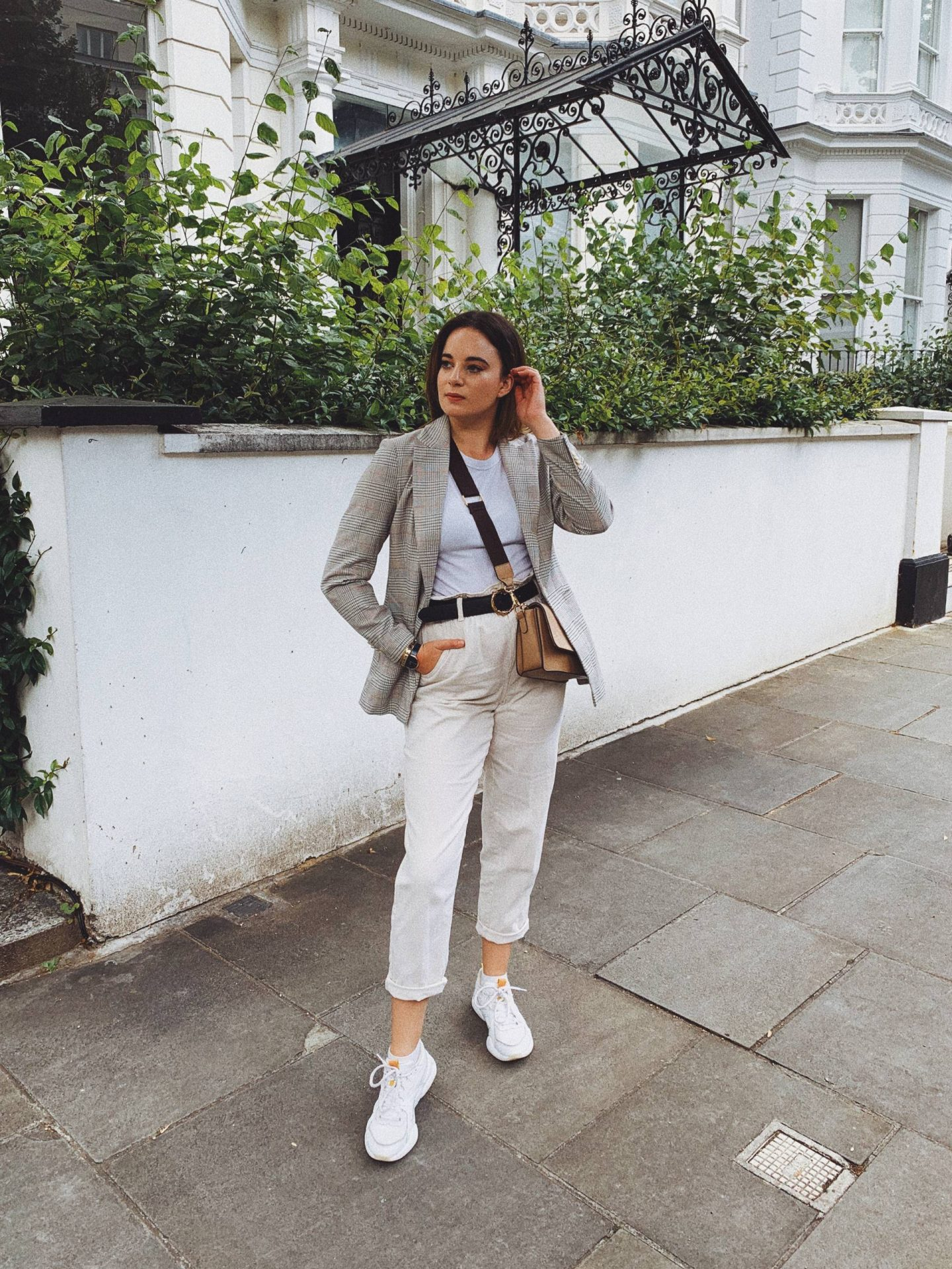 blazer and white trainers worn with cream jeans